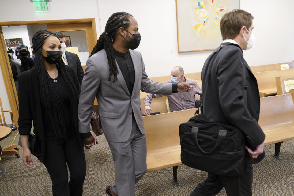 NFL football player Richard Sherman, center, heads into a hearing at King County District Court with his wife Ashley Sherman, left, and attorney Cooper Offenbecher, Friday, July 16, 2021, in Seattle. Prosecutors in Washington state have charged Sherman, who has played for the Seattle Seahawks and the San Francisco 49ers NFL football teams, after police said he drunkenly crashed his SUV in a construction zone and tried to break into his in-laws' home. (AP Photo/Ted S. Warren)