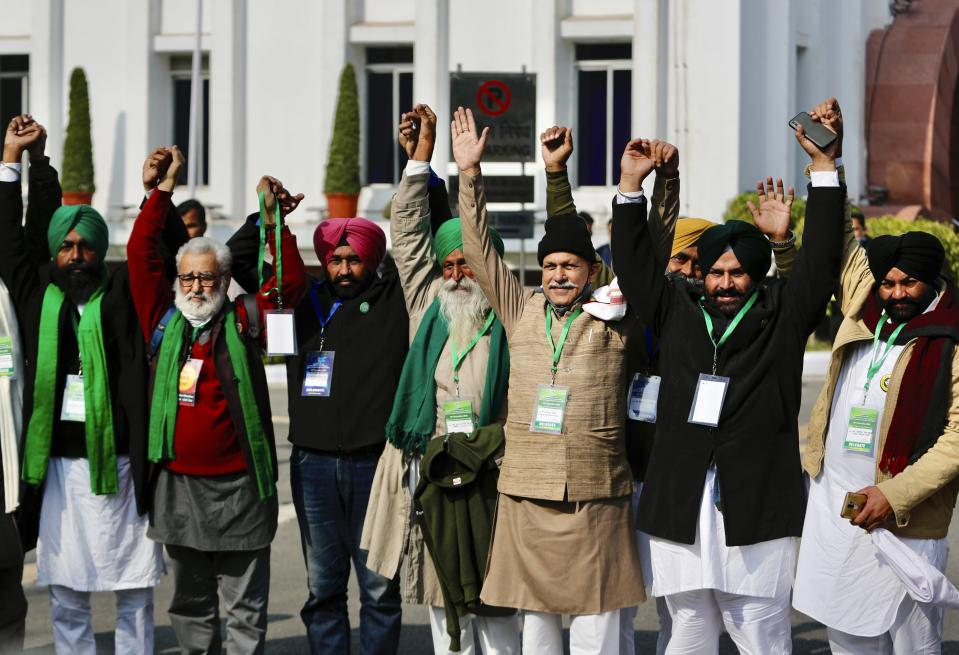 Farmer leaders raise their hands together before going in for a meeting with government representatives in New Delhi, India, Wednesday, Dec. 30, 2020. Protesting farmers fear the government will stop buying grain at minimum guaranteed prices and corporations will then push down prices. The government says the three laws approved by Parliament in September will enable farmers to market their produce and boost production through private investment. (AP Photo/Manish Swarup)