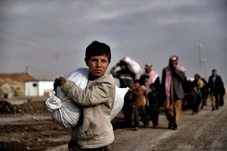 Residents of west Mosul flee the city on March 14, 2017, among more than 150,000 that have been displaced by the offensive government forces launched against the Islamic State group last month