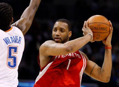 FILE PHOTO: Houston Rockets guard Tracy McGrady (R) keeps the ball from Oklahoma City Thunder guard Kyle Weaver in the first half during their NBA basketball game in Oklahoma City, Oklahoma, January 9, 2009. REUTERS/Bill Waugh