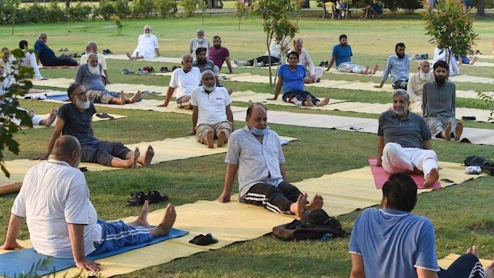 People practice Yoga ahead of the International Yoga day in Lahore on June 20, 2021.