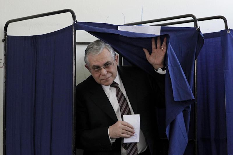 Greek Prime Minister Lucas Papademos leaves the booth to cast his vote at at a voting center , in Athens, Sunday, May 6, 2012.  Greeks cast their ballots on Sunday in their most critical and uncertain elections in decades, with voters seemingly set to punish the two main parties that are being held responsible for the country's dire economic straits.(AP Photo/Petros Giannakouris)