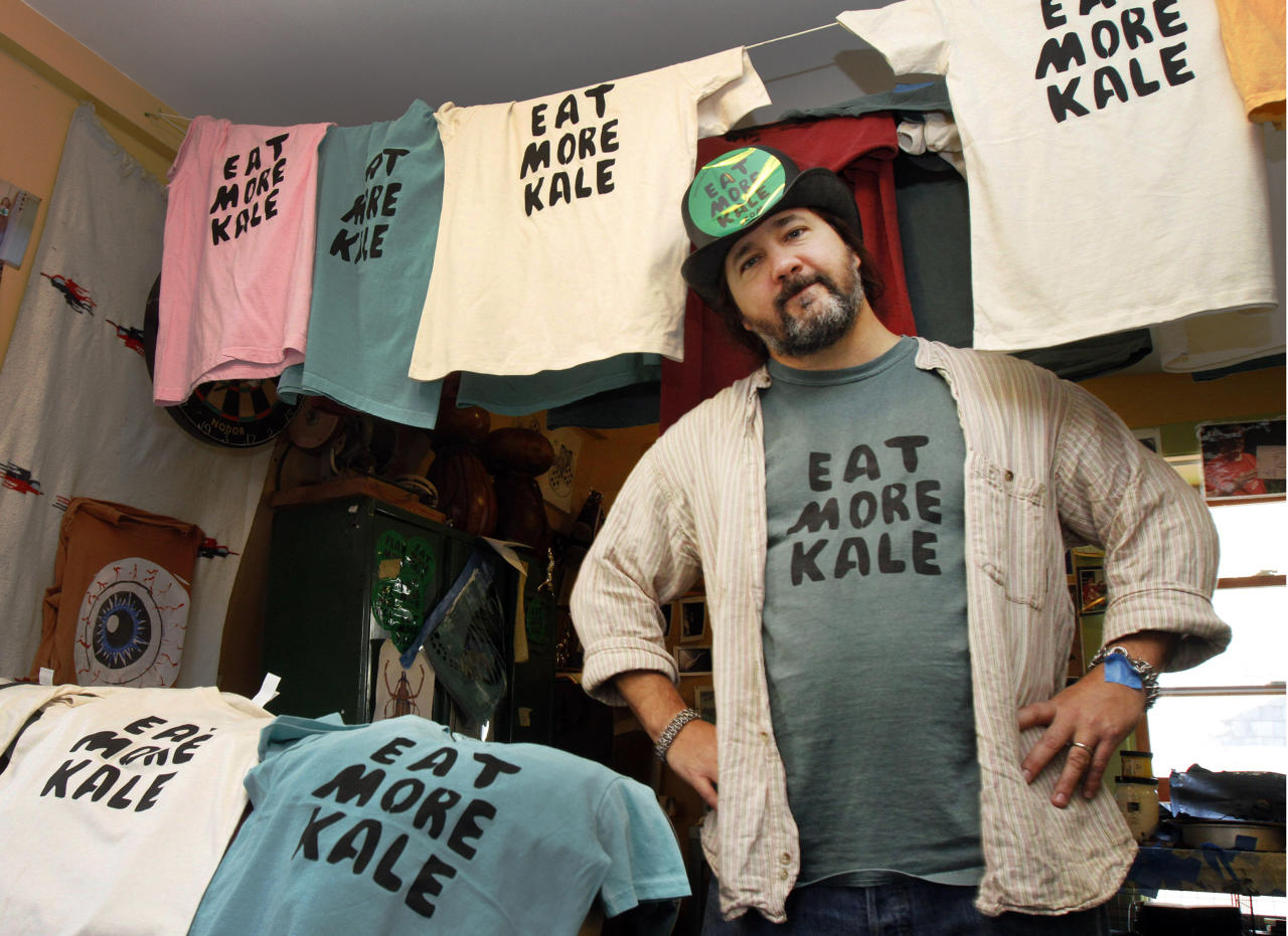 """FILE- In this Nov. 22, 2011 file photo, Bo Muller-Moore stands in his home studio in Montpelier, Vt. Muller-Moore, the Vermont man who is building a business around the term """"eat more kale,"""" which has been plastered on T-shirts, bumper stickers and other items, is ran into opposition this year from the second largest fried chicken retailer in the country, Chick-fil-A. (AP Photo/Toby Talbot, File)"""