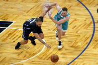 Orlando Magic guard Evan Fournier, left, and Charlotte Hornets forward Gordon Hayward go after a loose ball during the second half of an NBA basketball game, Monday, Jan. 25, 2021, in Orlando, Fla. (AP Photo/John Raoux)