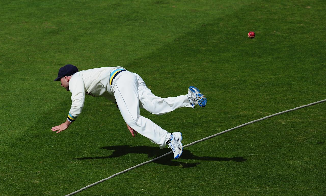 CHESTER-LE-STREET, ENGLAND - APRIL 26:  Yorkshire fielder Adam Lyth acrobatically stops a ball going for four runs during day three of the LV County Championship division One match between Durham and Yorkshire at The Riverside on April 26, 2013 in Chester-le-Street, England.  (Photo by Stu Forster/Getty Images)