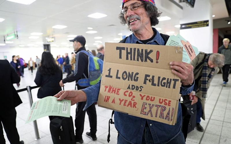 A protester hands out leaflets in the South Terminal at Gatwick Airport - PA