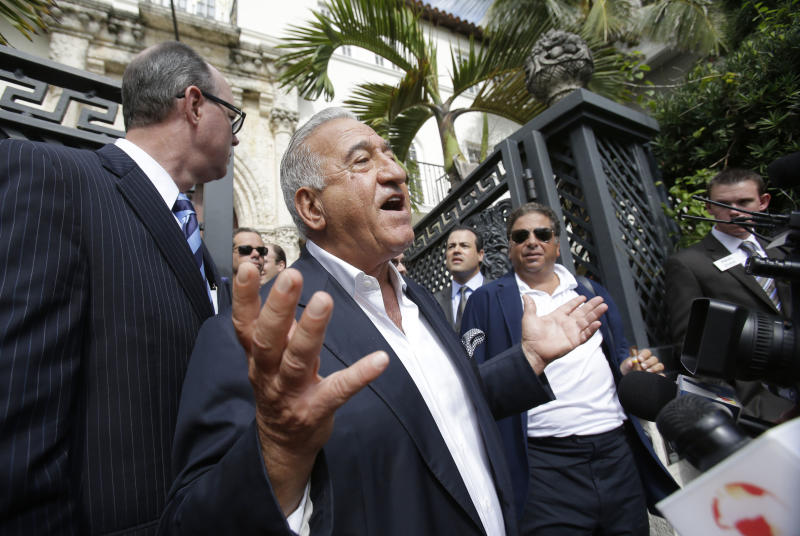 Joe Nakash, center, with VM South Beach LLC, speaks to the media after having placed the winning bid of $41.5 million for the South Beach mansion that once belonged to Gianni Versace, at rear, during an auction, Tuesday, Sept. 17, 2013 in Miami Beach, Fla. Gianni Versace bought the property in 1992. He was fatally shot on its steps in 1997 by a serial killer. His family sold it in 2000, and it operated as a private club and then as a boutique hotel until earlier this year. (AP Photo/Wilfredo Lee)