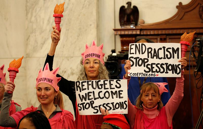 Protesters with Code Pink hold signs at the Senate Judiciary Committee confirmation hearing for Sen. Jeff Sessions (R-Ala.) to become U.S. attorney general on Jan.10. (Kevin Lamarque / Reuters)