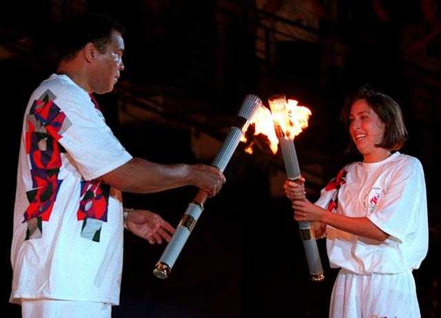 American swimmer Janet Evans passes the Olympic flame to Muhammad Ali during the 1996 Summer Olympic Games Opening Ceremony in Atlanta Friday, July 19, 1996. (AP Photo/Michael Probst)