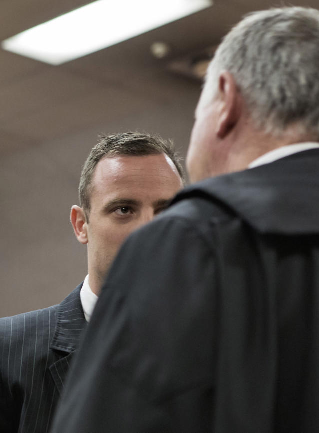 Oscar Pistorius, talks with his defense attorney, Barry Roux, right, in court in Pretoria, South Africa, Tuesday, March 18, 2014. Pistorius is on trial for the murder of his girlfriend Reeva Steenkamp on Valentines Day, 2013. (AP Photo/Marco Longari, Pool)