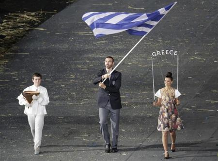 Greece's flag bearer Alexandros Nikolaidis holds the national flag as he leads the contingent in the athletes parade during the opening ceremony of the London 2012 Olympic Games at the Olympic Stadium July 27, 2012. REUTERS/Max Rossi