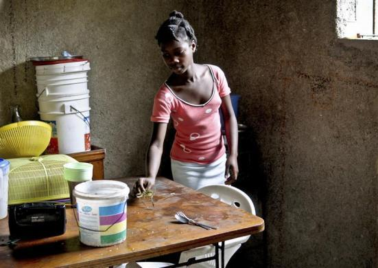 Haitian girl Fabien Destine (R), 14, who suffers from VSP congenital heart disease, or a hole in the chamber wall, does light chores at home in Port-au-Prince, March 24, 2012.