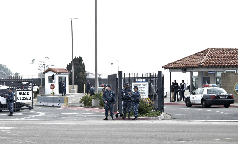 Military police stand guard outside Naval Base Point Loma in San Diego as San Diego police officers and federal agents search for former Los Angeles officer Christopher Dorner who police believe is responsible for three murders Thursday Feb. 7, 2013. Thousands of police officers throughout Southern California and Nevada searched for Dorner, who was angry over his firing and began a deadly shooting rampage that he warned in an online posting would target those on the force who wronged him. (AP Photo/Lenny Ignelzi)