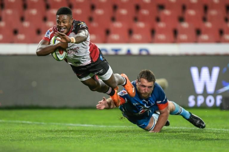 Lions centre Wandisile Simelane (L) scores a try after evading Bulls prop Gerhard Steenkamp during a South African Super Rugby Unlocked match at Ellis Park in Johannesburg Saturday.