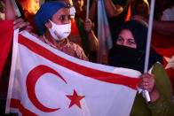 Supporters of the newly elected Turkish Cypriot leader Ersin Tatar hold a Turkish Cypriot breakaway flag and celebrate with others, in the Turkish occupied area in the north part of the divided capital Nicosia, Cyprus, Sunday, Oct. 18, 2020. Ersin Tatar, a hardliner who favors even closer ties with Turkey and a tougher stance with rival Greek Cypriots in peace talks has defeated the leftist incumbent in the Turkish Cypriot leadership runoff. (AP Photo/Nedim Enginsoy)
