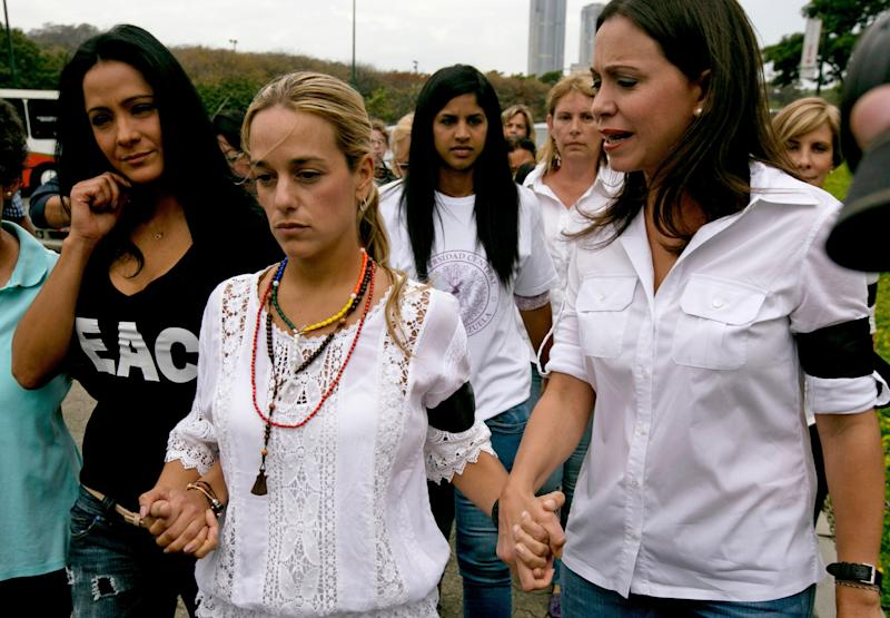 """Lilian Tintori, the wife of jailed opposition leader Leopoldo Lopez, center, walks hand in hand with actress Norkys Batista, left, and congresswoman Maria Corina Machado as they arrive for a news conference at Plaza Venezuela in Caracas, Venezuela, Monday, Feb. 24, 2014. Tintori said her husband Lopez believes the time is not right for members of the opposition to sit down with Venezuela's President Nicolas Maduro. Lopez """"thinks that Venezuela is not going to stop, that the discontent is nationwide, that it is a little late to call for peace,"""" she said. The news conference was called to announce a march on Wednesday by opposition women. (AP Photo/Fernando Llano)"""