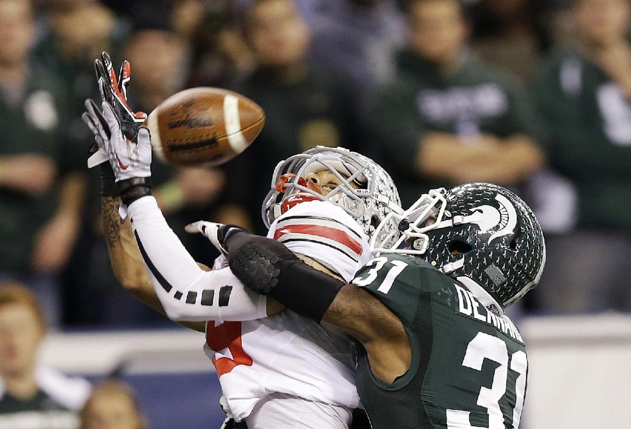 Michigan State's Darqueze Dennard (31) breaks up a pass intended by Ohio State's Devin Smith during the second half of a Big Ten Conference championship NCAA college football game Saturday, Dec. 7, 2013, in Indianapolis. (AP Photo/Michael Conroy)