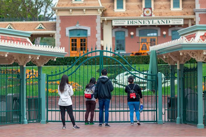 People stand outside the gates of Disneyland Park on Saturday, the first day of the closure of Disneyland and Disney California Adventure theme parks.