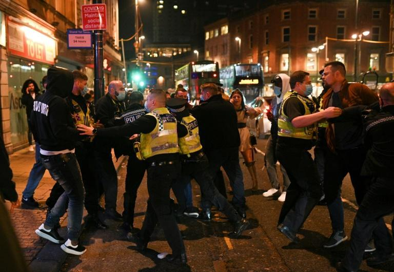 Police officers scuffled with revellers after pubs closed shortly before the start of the fresh lockdown