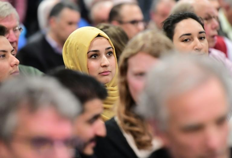 A woman looks on as people take part in a debate on role of Islam in the country at Rotterdam's Essalam mosque on March 10, 2017, ahead of the Dutch parliamentary elections