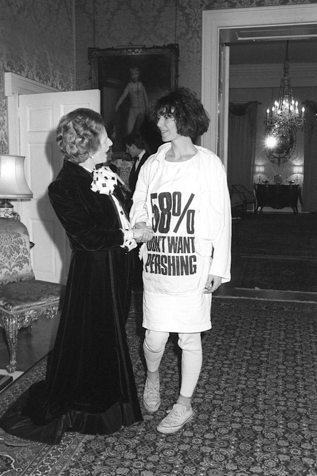 <p>Margaret Thatcher greets fashion designer Katharine Hamnett, wearing a t-shirt with a nuclear missile protest message, at 10 Downing Street, where she hosted a reception for British Fashion Week designers. [Photo: PA] </p>