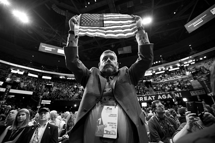 <p>Joseph Rice, an Oregon delegate, holds up the American flag. (Photo: Khue Bui for Yahoo News)</p>