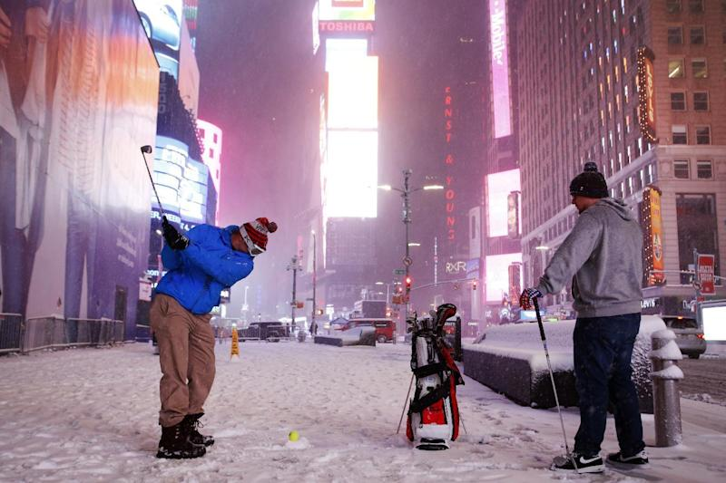 Two men play golf with a tennis ball as a snowstorm sweeps through Times Square, Tuesday, March 14, 2017, in New York. A powerful nor'easter hit the Northeast on Tuesday after a largely uneventful winter, grounding thousands of flights and leading to school and work closures along the coast. (AP Photo/Mark Lennihan)