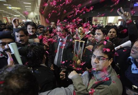 Cricket fans shower rose petals on Zaka Ashraf, chairman of the Pakistan Cricket Board (PCB), and team members after their arrival from India at Allama Iqbal International airport in Lahore January 7, 2013. REUTERS/Mohsin Raza