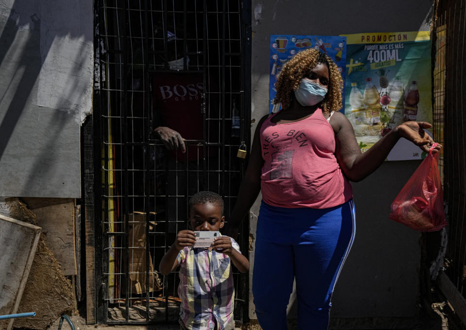 """Chilean-born Moises holds the Chilean, government-issued identification card of his dad Edanold Delva, next to his mother Jaqueline Michel, who also has permanent residency, outside their home in the Bosque Hermoso camp settled by migrants in Lampa, Chile, Friday, Oct. 1, 2021. Despite having a permanent residency visa, she says that in Immigration they ask for """"a bank certificate and a proof of residence"""" which she cannot get because she lives in an illegal land occupation. (AP Photo/Esteban Felix)"""