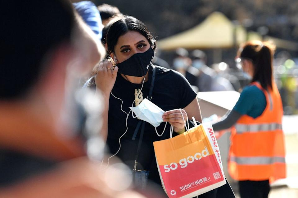 A girl adjusts her mask as she waits in a queue for Covid-19 coronavirus vaccination in Sydney.