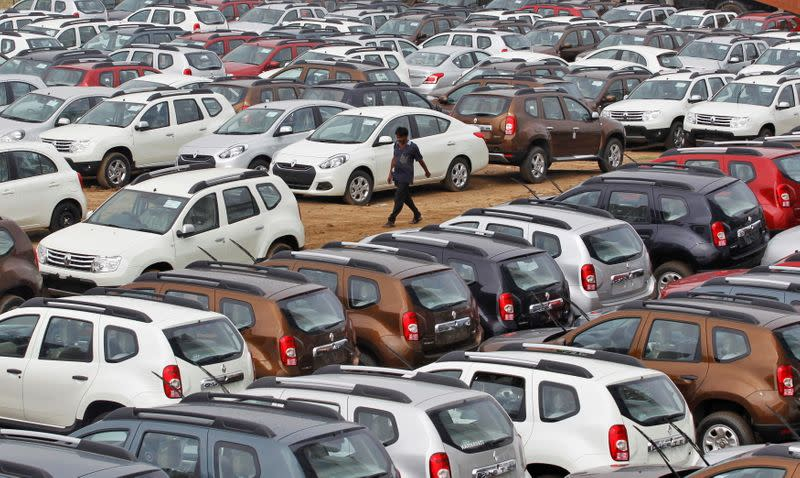 FILE PHOTO: A worker walks past parked Renault cars at its stockyard on the outskirts of Ahmedabad