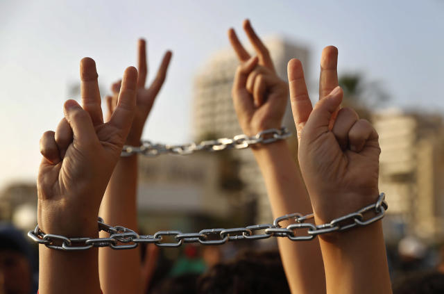 <p>Palestinian boys raise their hands, in chains, during a protest to show their solidarity with Palestinian prisoners in Israeli jails who have been on an open-ended hunger strike for the past 18 days, in Beirut, Lebanon, May 4, 2017. (Photo: Hussein Malla/AP) </p>