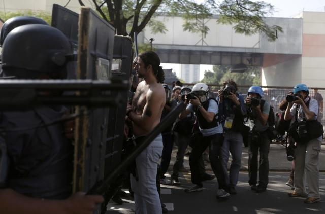 Media take pictures of a demonstrator facing riot policemen during a protest against the 2014 World Cup in Sao Paulo June 12, 2014. REUTERS/Ricardo Moraes (BRAZIL - Tags: SPORT SOCCER WORLD CUP CIVIL UNREST MEDIA)