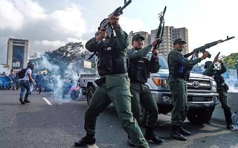 Members of the Bolivarian National Guard who joined Venezuelan opposition leader and self-proclaimed acting president Juan Guaido fire into the air to repel forces loyal to President Nicolas Maduro - Credit: AFP