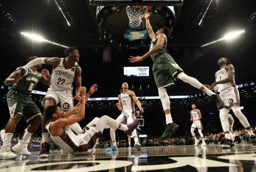 Milwaukee's NBA Most Valuable Player Giannis Antetokounmpo shoots against Brooklyn's Spencer Dinwiddie in a 117-97 victory over the Nets