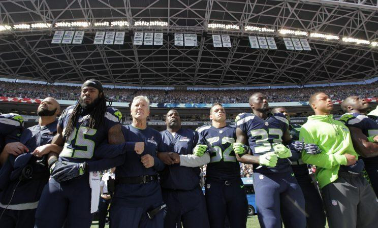 Richard Sherman (25) and the Seattle Seahawks locked arms during the national anthem in a sign of unity (AP)