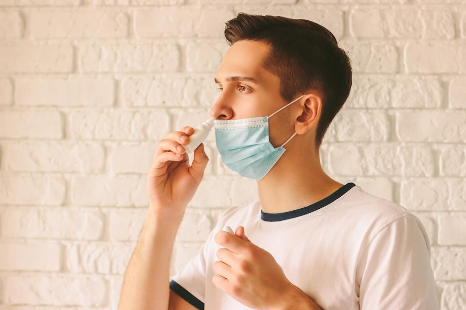 Portrait of young sick man using nasal drops for runny congested nose. Confident sick doctor in medical protective mask on face using nose spray. Pandemic coronavirus COVID-19 nCov-19 symptoms