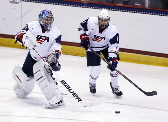 USA goalie Jessie Vetter (31) passes the puck to USA's Lisa Chesson (11) during the first period of a Four Nations Cup women's hockey game against Sweden on Tuesday, Nov. 5, 2013, in Lake Placid, N.Y. (AP Photo/Mike Groll)