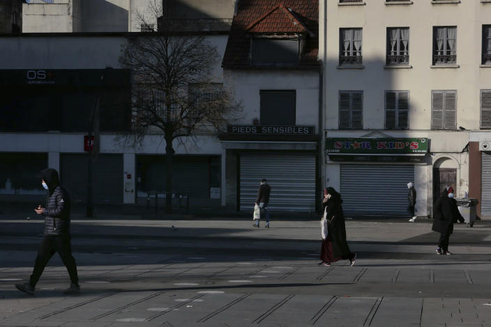 People walk in a street of Saint-Denis, north of Paris, Monday, Jan. 25, 2021. Many people lining up for vaccines in the Paris suburb are particularly grateful for the injections. The surrounding region is the poorest in mainland France, with 130 languages spoken and the country's highest rise in mortality last spring. (AP Photo/Christophe Ena)