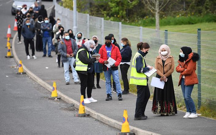 Members of the public queue at a temporary Covid-19 vaccination centre at the Essa academy in Bolton - Oli Scarff/AFP