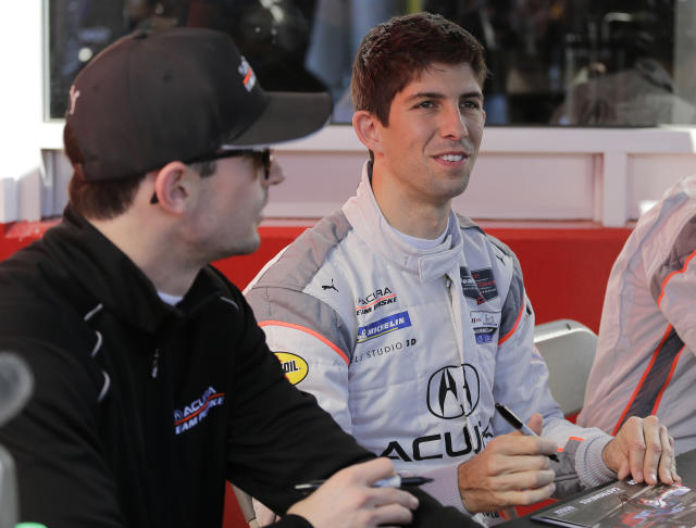 Acura Team Penske driver Ricky Taylor, right, signs autographs as teammate Alexander Rossi looks on, before the Rolex 24 hour auto race at Daytona International Speedway, Saturday, Jan. 25, 2020, in Daytona Beach, Fla. (AP Photo/Terry Renna)