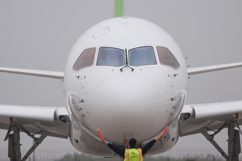A member of staff gives signal in front of China's home-grown C919 passenger jet after it landed on its maiden flight at the Pudong International Airport in Shanghai, Friday, May 5, 2017. The first large Chinese-made passenger jetliner C919 took off Friday on its maiden flight, a symbolic milestone in China's long-term goal to break into the Western-dominated aircraft market. (Aly Song/Pool Photo via AP)