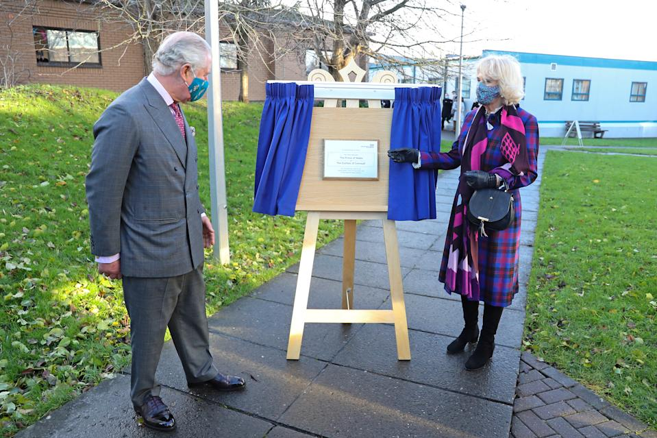 GLOUCESTER, ENGLAND - DECEMBER 17: Prince Charles, Prince of Wales and Camilla, Duchess of Cornwall unveiling a plaque to commemorate their visit to Gloucestershire Vaccination Centre at Gloucestershire Royal Hospital on December 17, 2020 in Gloucester, England. Gloucestershire Hospitals NHS Foundation Trust is one of the largest non-specialist Trust's in England, The Trust is the designated Management and Coordination Centre for the roll out of the COVID-19 Vaccination Programme for Gloucestershire. Their Royal Highnesses The Prince of Wales and The Duchess of Cornwall previously visited Gloucestershire Royal Hospital in June of this year, the first engagement outside of a Royal residence by any Member of the Royal Family following the first national lockdown. (Photo by Chris Jackson/Getty Images)