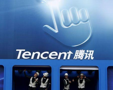 Dancers perform underneath logo of Tencent at Global Mobile Internet Conference in Beijing