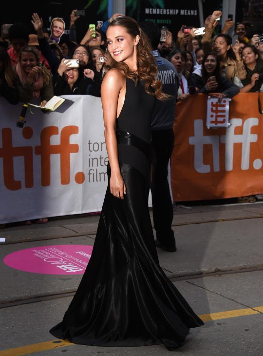 "<p>At the Toronto premiere of the already acclaimed ""The Danish Girl,"" Alicia Vikander shined in a satin Louis Vuitton gown accented with panels made of just as shiny material.</p>"