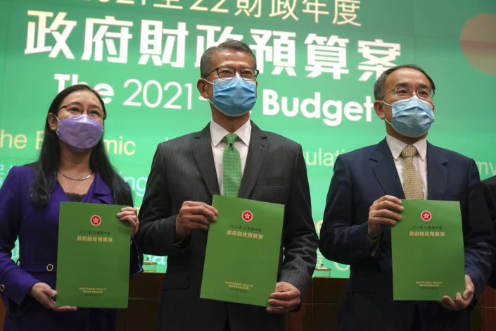 Hong Kong Finance Minister Paul Chan, center, attends a press conference on budget for 2021-22 in Hong Kong, Wednesday, Feb, 24, 2021. Hong Kong will introduce 120 billion Hong Kong dollars ($15.4 billion) in fiscal measures to help businesses and residents impacted by the coronavirus pandemic, as it looks towards economic growth later this year following a recession in 2020. (AP Photo/Kin Cheung)