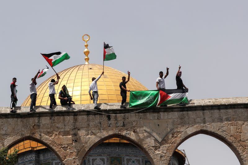 Palestinians hold flags as they stand at the compound that houses Al-Aqsa Mosque in Jerusalem's Old City