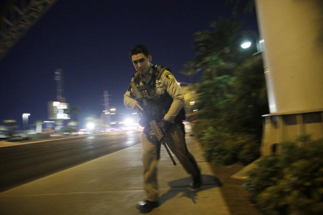 <p>A police officer runs along a sidewalk near a shooting near the Mandalay Bay resort and casino on the Las Vegas Strip, Oct. 1, 2017, in Las Vegas. (Photo: John Locher/AP) </p>