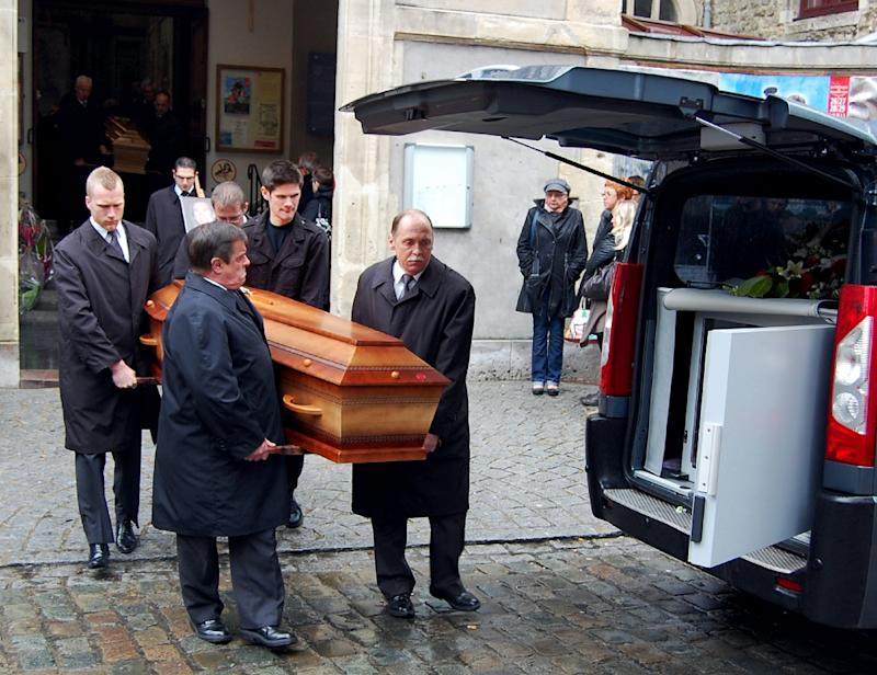 Funeral service employees carry coffins of Gerald Fontaine and Johanna Delahaye, on May 5, 2012, murdered in Madagascar
