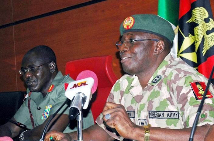 New head of the five-nation Multi-National Joint Task Force Major-General Iliya Abbah (R) speaks, flanked by his predecessor Nigerian army chief Major General Tukur Buratai, during a handover ceremony in Abuja on July 31, 2015 (AFP Photo/)